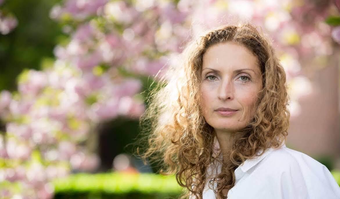 Portrait of Doro Erichsen with pink flowers in background