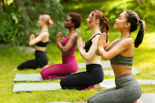 Multicultural girls doing yoga in park